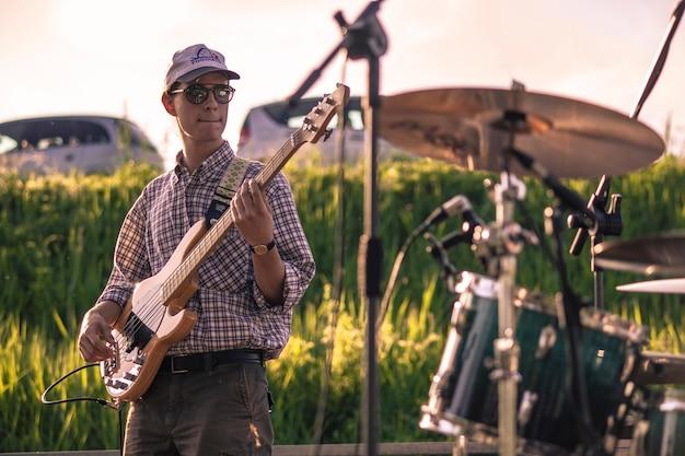 Basista szarpie akustyczne struny basowe podczas występu na żywo