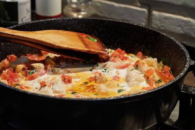Bass z pomidorami kopru włoskiego i bazylią smaży się na patelni na kuchence gazowej.