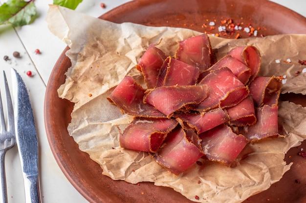 Basturma - jerky, zakąska mięsna do piwa na talerzu, close-up