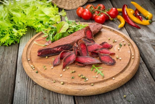 Basturma ormiańska. wołowina peklowana i przyprawa. produkty ekologiczne na drewnianym stole