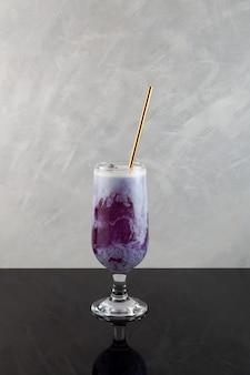 Batat latte z kostkami lodu fioletowy koktajl podawany ze słomką letni napój orzeźwiający