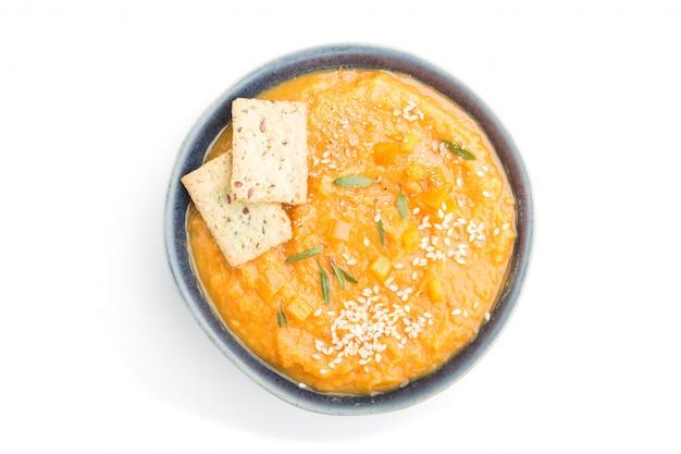 Batat lub batata kremowa zupa z sezamem i przekąski w niebieskich miseczkach ceramicznych na białym tle. widok z góry, z bliska.