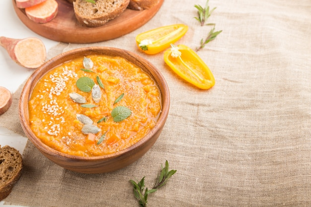Batat lub batata kremowa zupa z sezamem w drewnianej misce na białym tle drewnianych. widok z boku, selektywne focus, miejsce.