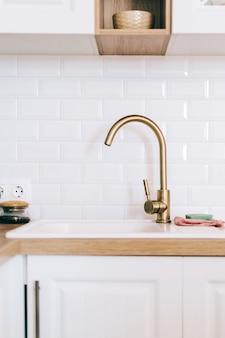 Bateria w kolorze złotym lub kran z metalową umywalką w kuchni.