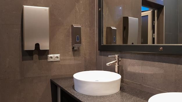 Baterie chromowane z białymi okrągłymi umywalkami w toalecie publicznej z dużym lustrem i szarymi ścianami, nowoczesne wnętrze toalety publicznej.