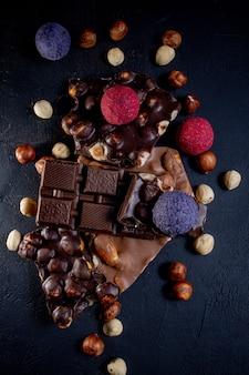 Baton czekoladowy, pokruszone kawałki gorzkiej czekolady i orzechy. czekoladowe cukierki pralinowe.