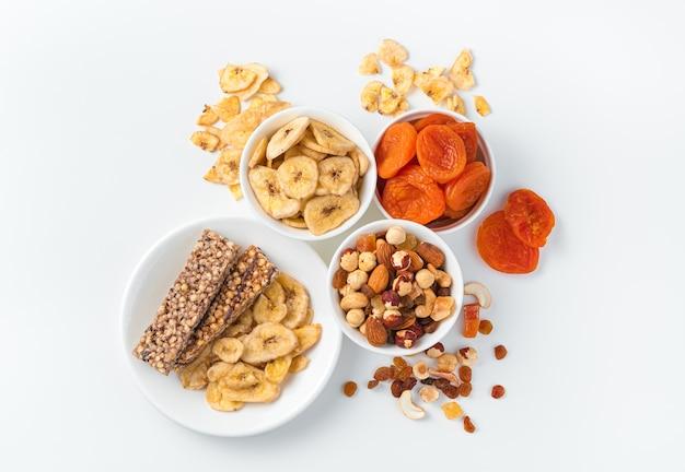 Baton granola, orzechy i suszone owoce na lekkiej ścianie z białymi talerzami. widok z góry, poziomy. naturalne, zdrowe słodycze.
