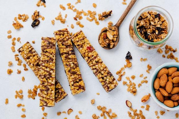 Baton zbożowy granola z orzechami, owocami i jagodami na białym kamiennym stole. baton granola. zdrowa przekąska. widok z góry.