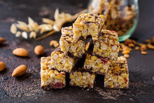 Baton zbożowy granola z orzechami, owocami i jagodami na ciemnym kamiennym stole. baton granola. zdrowa przekąska. widok z góry.
