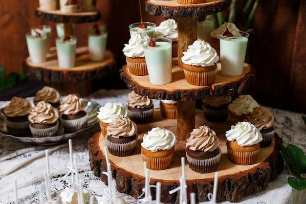 Batonik na drewnianym przyjęciu weselnym z wieloma różnymi cukierkami, babeczkami, sufletem i ciastami