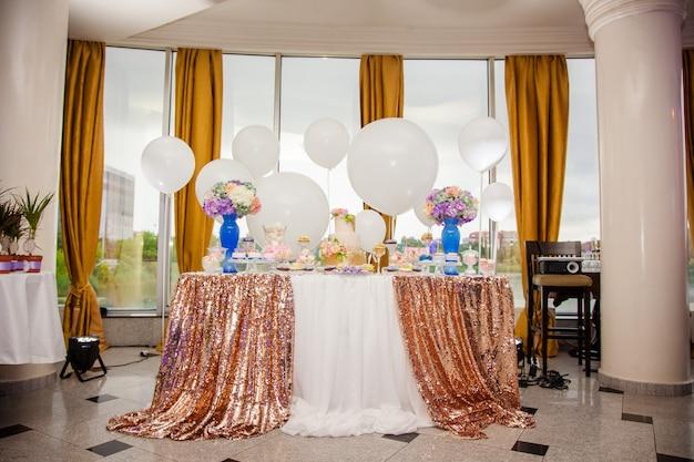 Batonik na złotym przyjęciu weselnym z dużą ilością różnych cukierków, babeczek, sufletów i ciast.