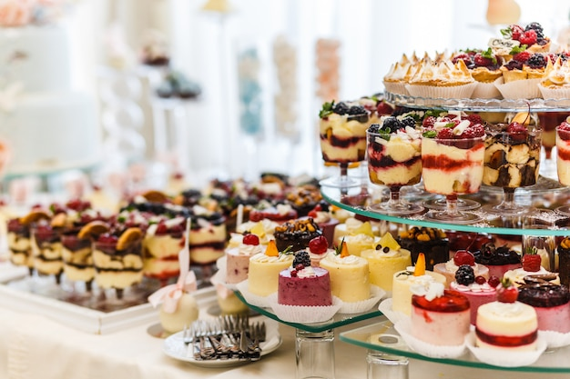 Batonik. stół z różnymi słodyczami na imprezę. deserowy stół na przyjęcie weselne. zdobione pyszne. słodycze, cukierki, deser, babeczki, tartaletki, makaroniki, ciasta i babeczki.
