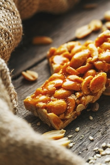 Batonik z orzeszkami ziemnymi. pyszne orientalne słodycze gozinaki z nasion słonecznika, sezamu i orzeszków ziemnych, pokryte miodem z błyszczącym lukrem