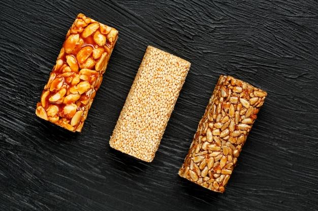 Batonik zbożowy z orzeszków ziemnych, sezamu i słonecznika na desce do krojenia na ciemnym kamiennym stole. widok z góry. trzy różne paski