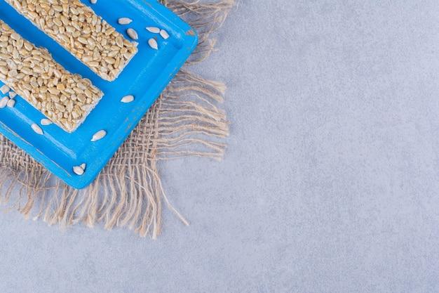 Batoniki granola na drewnianym talerzu na marmurze.