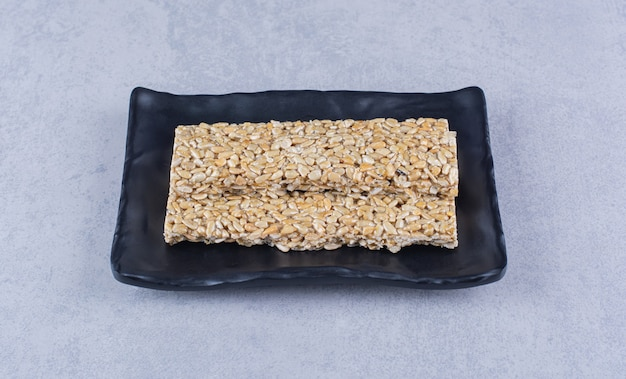 Batoniki granola na talerzu na marmurowej powierzchni