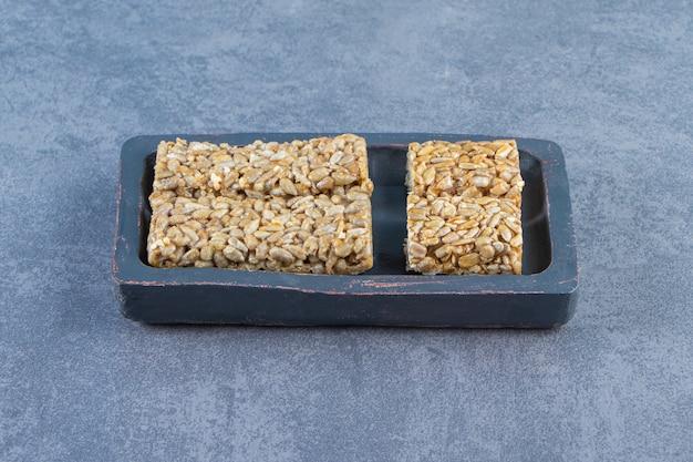 Batoniki granola w drewnianym talerzu, na marmurowym tle.