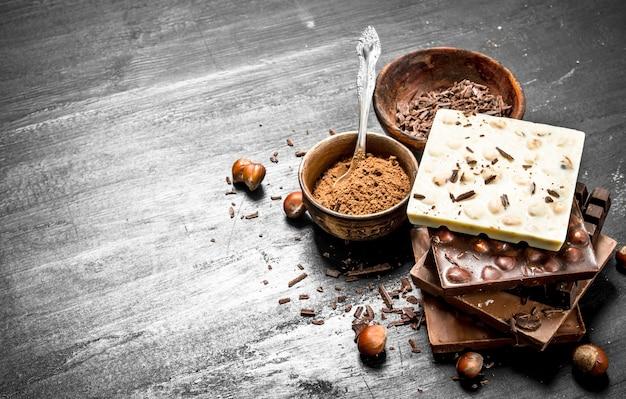 Batoniki różnych rodzajów czekolady z kakao w proszku. na czarnej tablicy.