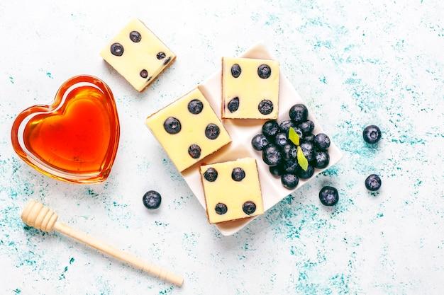 Batoniki sernikowe jagodowe z miodem i świeżymi jagodami.