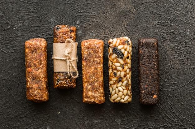 Batony miodowe z orzeszkami ziemnymi, sezamem i słonecznikiem orzechy karmelowe. przekąski z nasion, orzechów i sezamu z miodem na drewniane tła. orzechy cukrowe