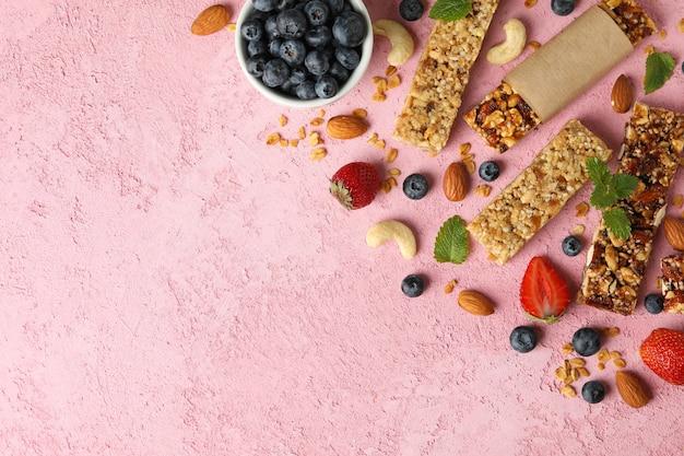 Batony muesli i miska z jagodami na różowym tle