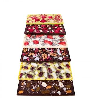 Batony wielokolorowej czekolady z sublimowanymi jagodami, orzechami kokosowymi i nasionami na białym tle.