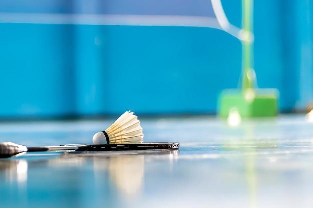 Batterie i transfer kogut badminton w niebieskim sądzie z gry w badmintona