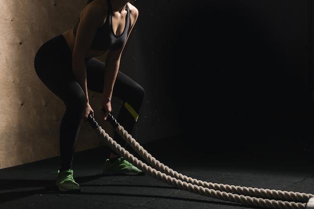 Battling liny dziewczyna na siłowni treningu ćwiczenia dopasowanego ciała