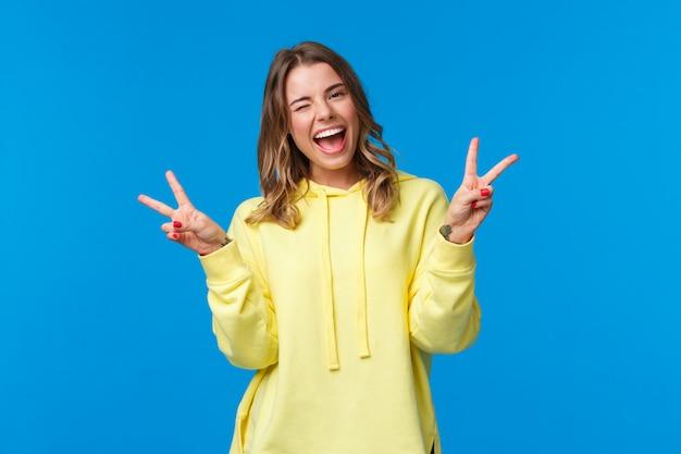 Baw się dobrze beztroska, optymistyczna, przyjazna kawaii blond dziewczyna w żółtej bluzie z kapturem, mrugająca i uśmiechnięta zęby, pokazujące słodkie gesty pokoju,