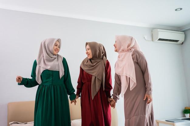Baw się, spędzając czas trzy muzułmańskie kobiety stojące w łóżku
