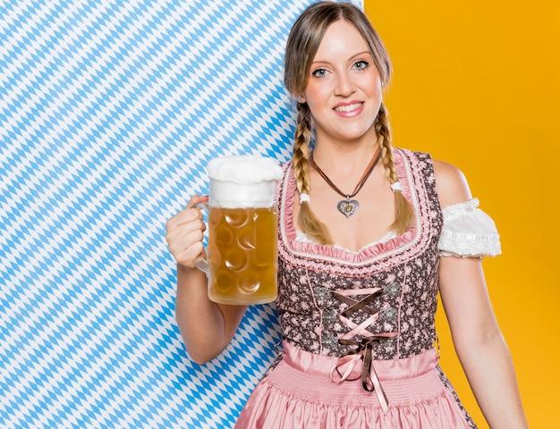 Bawarska kobieta trzyma piwnego kubek