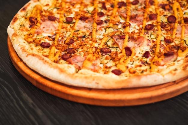 Bawarska Pizza, Na Okrągłej Tacy Na Drewnianym Stole Premium Zdjęcia
