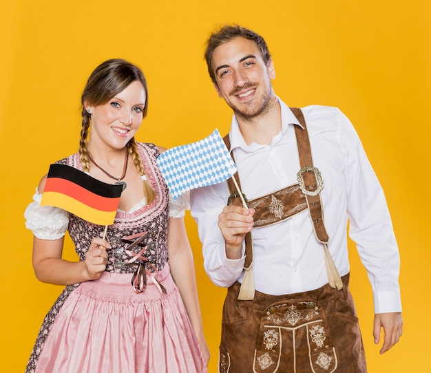 Bawarski mężczyzna i kobieta trzymając flagi