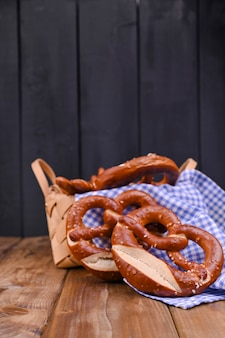 Bawarski precel ozdobiony niebiesko-białą tkaniną na rustykalnej drewnianej desce munich oktoberfest