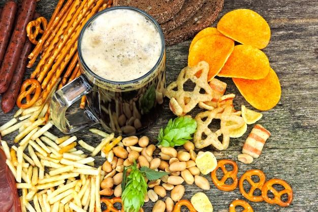 Bawarskie kiełbaski, szynka, chmiel, piwo, przekąski. kompozycja oktoberfest ze szklanką ciemnego piwa i piwnych przekąsek. precle, piwo, chmiel.