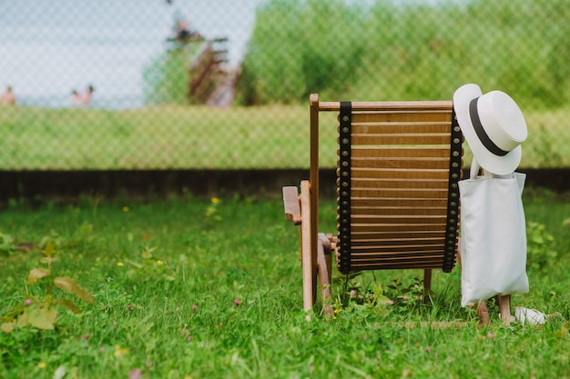 Bawełniana czapka z wikliny i eko torba obok drewnianego leżaka