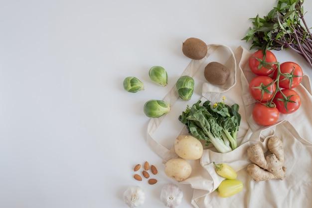 Bawełniana eco torba na zakupy ze świeżymi warzywami na płasko leżącym białym tle. z tworzywa sztucznego za darmo do zakupów i dostaw produktów spożywczych. styl życia zero marnotrawstwa. zdrowe jedzenie i dieta wegańska.