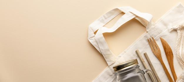 Bawełniana torba, bambusowa ceramika, szklany słoik, bambusowe szczoteczki do zębów, szczotka do włosów i słomki na kolor tła, leżał płasko.