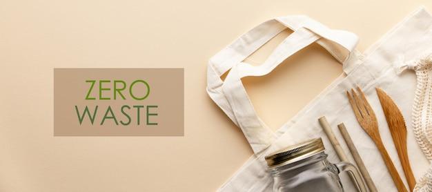 Bawełniana torba, bambusowa ceramika, szklany słoik, bambusowe szczoteczki do zębów, szczotka do włosów i słomki w kolorze, leżą płasko.