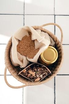 Bawełniana torba wielokrotnego użytku z nasionami lnu, szklanym słojem i domową granolą w papierowej torbie wszystko do koszyka