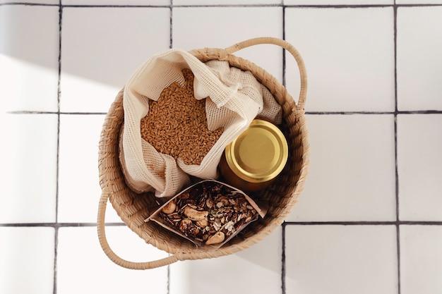 Bawełniana torba wielokrotnego użytku z nasionami, szklanym słojem i domową granolą w papierowej torbie, wszystko włożone do koszyka