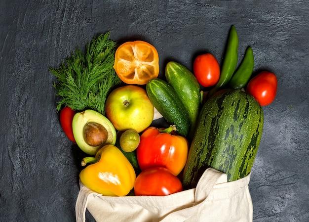 Bawełniana torba z warzywami i owocami. na stole leżało płaskie jedzenie.