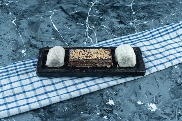 Bawełniane cukierki i wafel czekoladowy na drewnianym talerzu na ściereczce, na niebieskim tle.