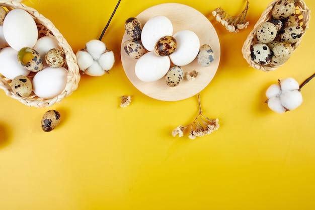 Bawełniane kwiaty i jajka przepiórcze w małych koszyczkach na fakturze tkaniny
