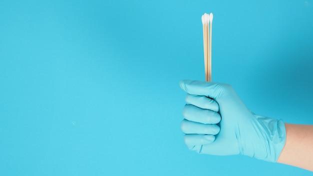 Bawełniane patyczki do ręki z niebieskimi rękawiczkami medycznymi lub lateksowymi rękawiczkami na niebieskim tle.covid-19 concept