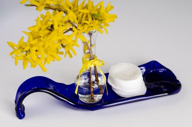 Bawełniane płatki i żółte kwiaty na niebieskiej płytce z butelki