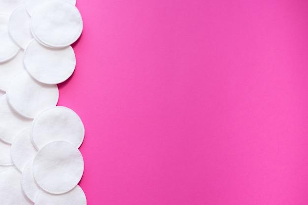 Bawełniane podkładki na różowym tle, top view.disk dla higieny twarzy piękna.