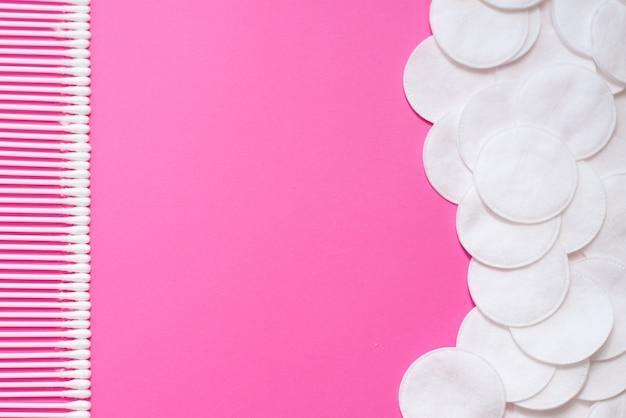 Bawełniane waciki i płatki kosmetyczne na różowym tle.