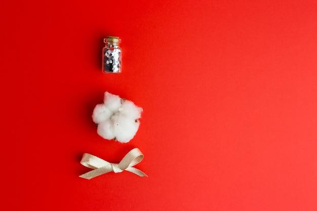Bawełniany kwiatek, szklana butelka z konfetti i kokardką na czerwonym tle.