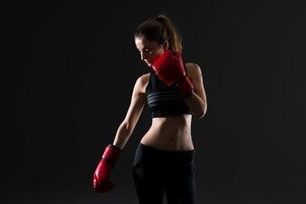 Bawi się kobiety z bokserskimi rękawiczkami na ciemnym tle